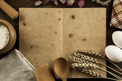 Open vintage book on the aged wooden background. Kitchen utensils, ears of wheat, flour in a pot. homemade, menu, recipe, mock Royalty Free Stock Photo