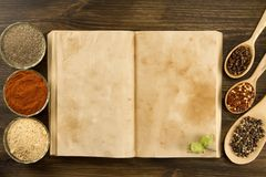 Open vintage book with spices on wooden background. Healthy vegetarian food. Stock Photos