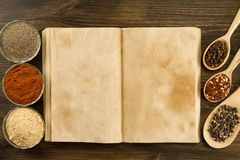 Open vintage book with spices on wooden background. Healthy vegetarian food. Recipe, menu, mock up, cooking. Royalty Free Stock Images