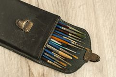 Leather case box with paint brushes closeup Stock Photos