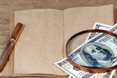 Open vintage notepad and Hundred dollar bill under magnifying gl Royalty Free Stock Image