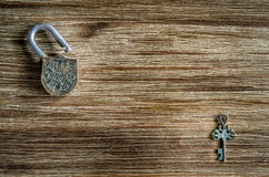 Open vintage padlock and key on a wooden texture Stock Photo