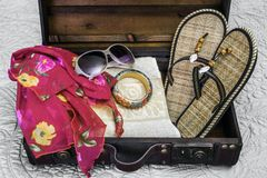 Open vintage suitcase packed with sandals, scarf, bracelet and s Stock Image