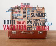Open vintage suitcase with icons. Open vintage suitcase with vacation icons and words Stock Photos