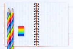 Open voorbeeldenboek met regenboog-gekleurde potloden en een rubber op witte houten lijst stock fotografie