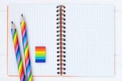 Open voorbeeldenboek met twee regenboog-gekleurde potloden en een rubber op witte houten lijst stock afbeelding