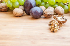 Open walnuts close up on wooden background and grapes and plums in the back Stock Photo