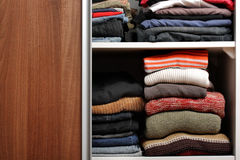 Open wardrobe with lots of folded clothes Royalty Free Stock Photography