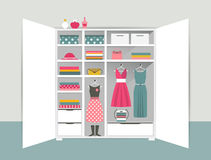 Open wardrobe. White closet with tidy clothes, shirts, sweaters, boxes and shoes. Home interior. Royalty Free Stock Photo