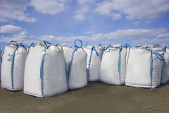 Open warehouse of big bags. Against the blue sky and clouds royalty free stock photo