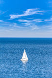 Open water with a yacht. Blue open water with a sailboat in summer Royalty Free Stock Photo
