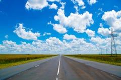 Open weg onder een briljante blauwe Afrikaanse hemel stock foto's