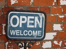Open and welcome sign with old red brick backround Stock Photo
