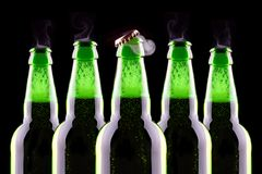 Open wet beer bottle. Isolated on black Stock Photos