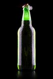 Open wet beer bottle. Isolated on black Royalty Free Stock Images