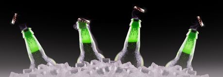 Open wet beer bottles on ice Royalty Free Stock Photos