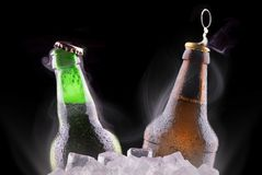 Open wet beer bottles on ice Stock Photography