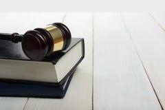 Open wetsboek met houten rechters binnen hamer op lijst Stock Foto's