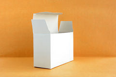 Open white cardboard box on light brown background Stock Photography