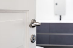 Open white door with metallic handle. Royalty Free Stock Images