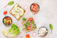 Open wholemeal sandwiches and various ingredients Stock Photography