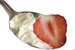 Open wide. Cut Strawberry and cream on a spoon Royalty Free Stock Images