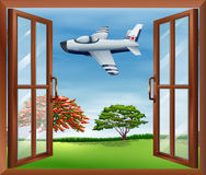 An open window with an airplane outside Stock Image