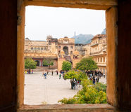 Open window of the Amber Fort and people walking around the historical stone palaces Stock Image