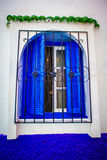 Open window with blue shutters and metal bars. On a white painted wall Royalty Free Stock Photography