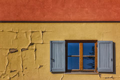 Open Window on Colorful Wall. Detail of an open window on a colorful wall in Italy Royalty Free Stock Image