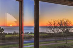 An open window, with a key lock and wood coloured frame catches the reflection of a sunset. Whilst beyond is a soft focus view of a promenade and sea stock photos