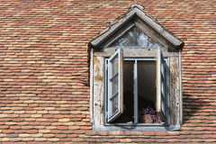 Open window in an old dormer on a roof with historic. Open window in an old dormer made of wood on a roof with historic beaver tail tiles, copy space Stock Photo