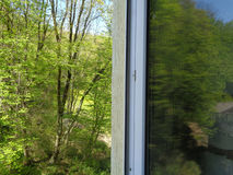 Open window overlooking spring forest. Green forest outside house window, reflection trees in glass Royalty Free Stock Photos