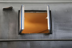 An open window in a steel wall with orange glow inside. An open window in the grey steel wall of a houseboat under construction with a warm orange glow inside stock images