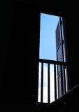 Open window to blue sky. An image of an old open wooden window looking out to a view of blue sky with white clouds. High contrast of dark black interior with the Stock Photos