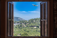 Open window with view of mountains and blue sky airplane. Stock Photos