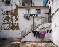 Open windows and linen. Elegant stories of the old Lisbon. Portugal. Alfama The streets of the old Portuguese city of Lisbon. The beauty of the old city. Linen royalty free stock photos