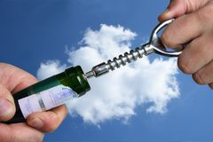 Open wine bottle. Man hands open wine bottle with corkscrew over blue sky Stock Photo