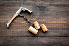 Open wine bottle. Corks and corkscrew on dark wooden background top view copyspace. Open wine bottle. Corks and corkscrew on dark wooden background top view stock photography