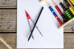 Open wiskundenotitieboekje met gekleurde tellende telraam en staalcompas Stock Foto's