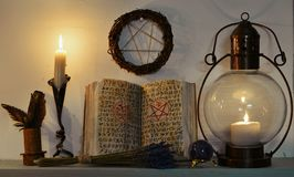 Open witch book with spells, old-fashioned lamp, candle and pentagram royalty free stock photos