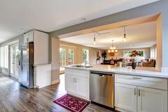 Open witte de keukenruimte van het vloerplan met opgepoetste hardhoutvloer Stock Afbeeldingen