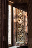 Open wooden door with carved thai style patterns Royalty Free Stock Images