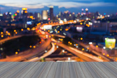 Open wooden floor with blurred bokeh city highway and city light Stock Photos