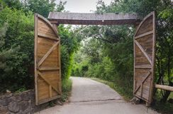 Open wooden gate in park. Open wooden gate on road in park stock images