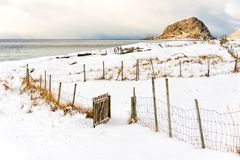 Open wooden gate on a snowy beach. Open wooden gate to a field on a snowy beach stock image