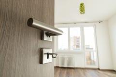 Open wooden oak door to modern empty room Royalty Free Stock Image