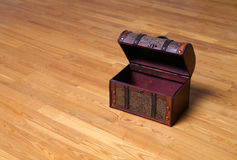 Open wooden vintage chest. With leather handle on parquet floor Stock Photography