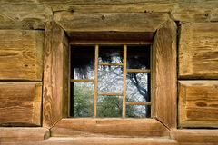 Open wooden window in yellow blockhouse wall Royalty Free Stock Photos
