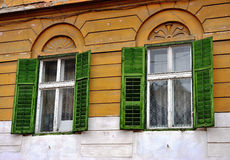 Open wooden windows with the green blinds Royalty Free Stock Images